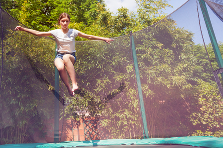 Portrait of teenage girl jumping on the trampoline with safety net in the backyard Stock Photo - 107813184
