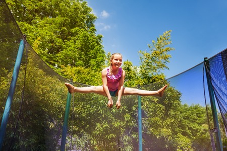 Low-angle portrait of preteen girl performing a split jump in the air, exercising on the trampoline outdoors Stock Photo