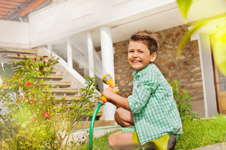 Little gardener watering plants at the backyard