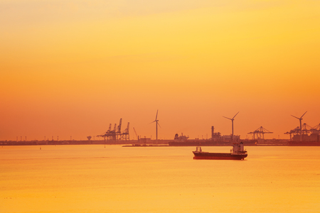 Port de Bouc petrochemical platform with wind turbines, portal cranes and tanker at twilight 写真素材
