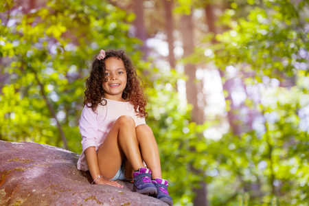 Portrait of smiling girl in forest sit on stone