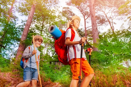 Two boys with backpacks on the hike in forest