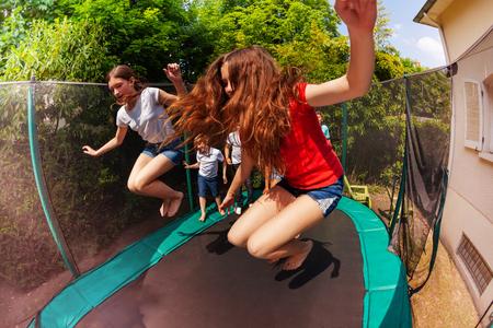 Niños y niñas saltando en el trampolín al aire libre Foto de archivo