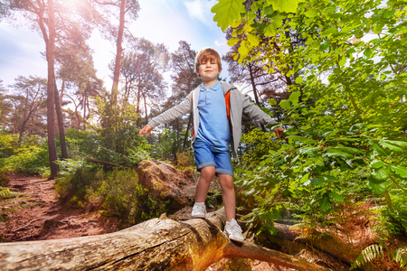 Small boy walks over log in forest with backpack