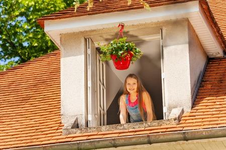 Smiling girl enjoying morning in the open window