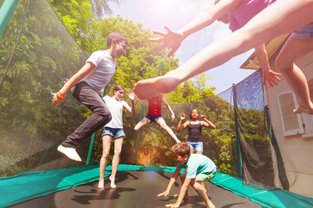 Boys and girls playing on the outdoor trampoline Standard-Bild