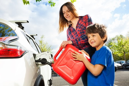Boy helping his mother to pour fuel into car tank