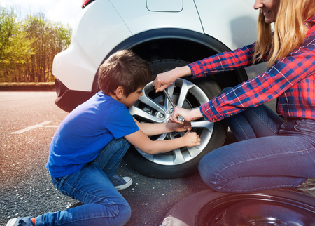 Boy helping mother to change tyre using lug wrench Stock fotó