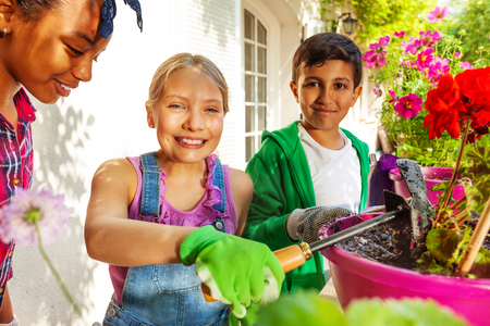 Cute girl working in garden with her friends Stock Photo