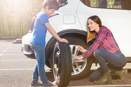 Little tyre mechanic helping mom to change a wheel 스톡 콘텐츠 - 107815811