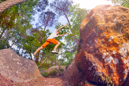 Boy jump from one rock to another in the forest Stock Photo