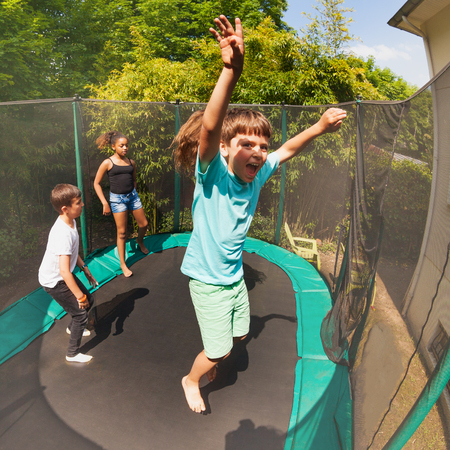 Excited boy jumping on the trampoline with friends