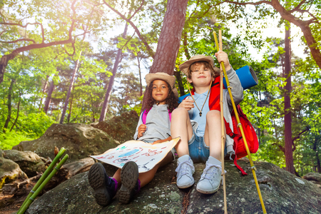 Kids rest during hike boy and girl with map Stock Photo