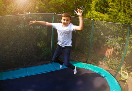 Happy boy jumping high on the backyard trampoline Stock fotó