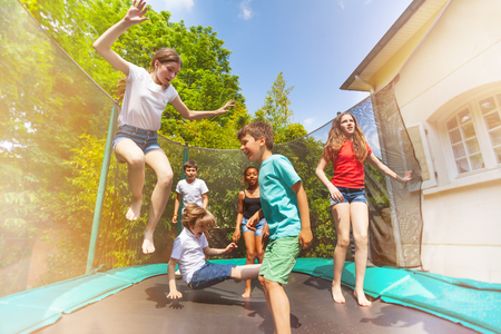 Happy children jumping on the outdoor trampoline