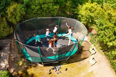 Boys and girls jumping on trampoline in the garden