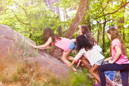 Group of kids climb on the rock in forest
