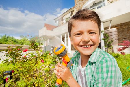 Smiling boy watering garden using hand sprinkler Stock Photo