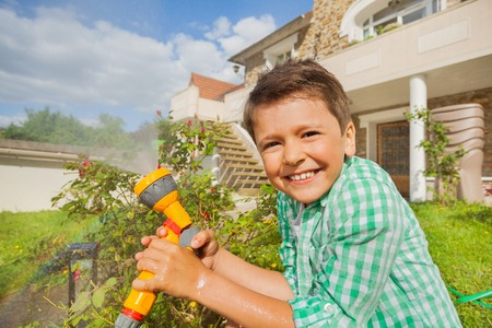 Happy boy watering garden with hand sprinkler Stock Photo