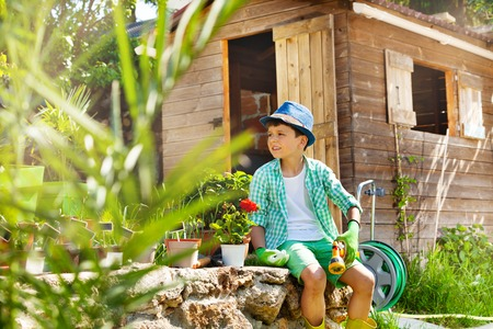 Little boy working in garden at sunny day Stock Photo