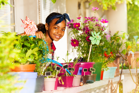 Happy African girl watering flowers on the balcony