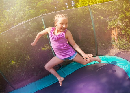 Cute girl having fun jumping on the trampoline 스톡 콘텐츠 - 107905337