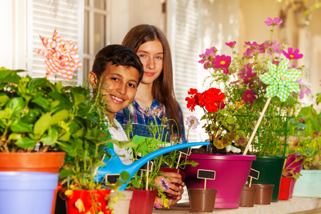 Happy children watering potted flowers on balcony Stock Photo