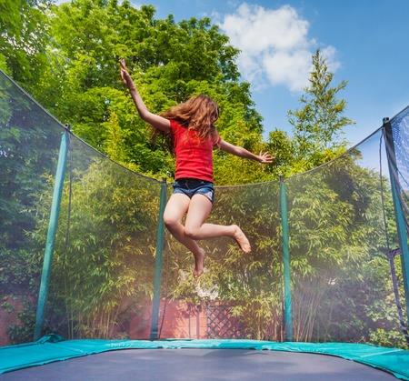 Active girl jumping on trampoline outdoors 스톡 콘텐츠 - 107905340