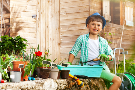Little gardener planting flowers in container