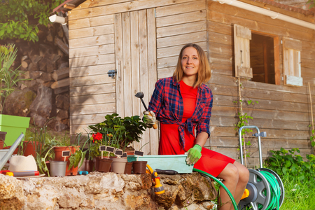 Beautiful young woman potting plants in the garden