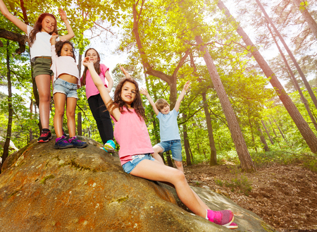 Group of small kids in the forest on a rock Stock Photo