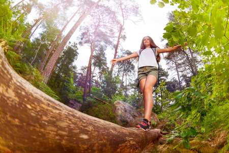 Girl walks over the log balancing with hands