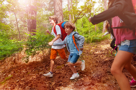 Two boys run in forest holding hands