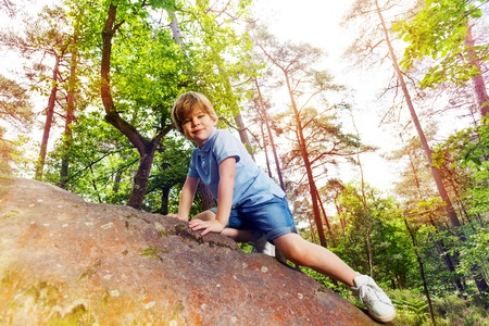Fun in the forest boy climbs on small stone Stock Photo