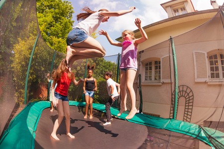Happy friends bouncing on the outdoor trampoline 写真素材