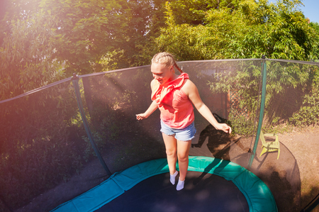 Happy girl jumping up and down on the trampoline