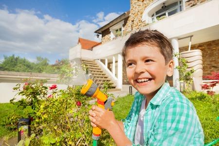 Cute boy watering garden with hand sprinkler Stock Photo