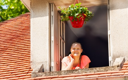 Happy girl looking out the attic window at street