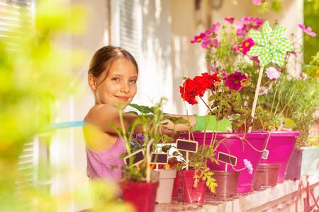 Adorable girl potting red geranium on the balcony