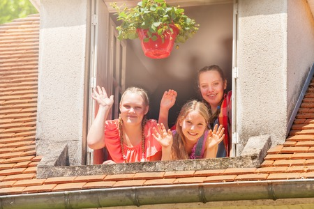 Girls waving hands, looking out the attic window