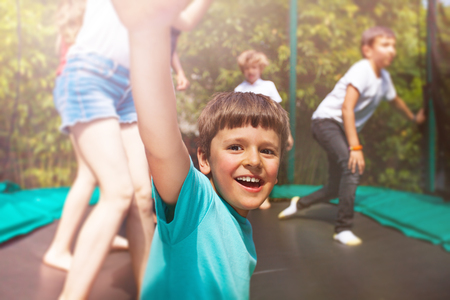 Happy boy jumping on trampoline with his friends Stock Photo