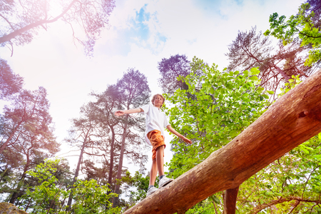 Boy walks over the high log in forest hold balance Stock Photo