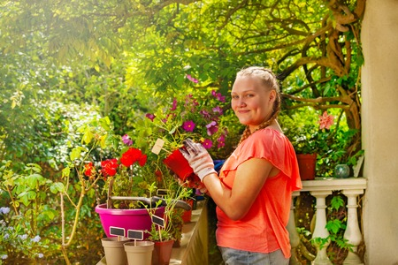 Girl standing on balcony with potted flowers Stock Photo