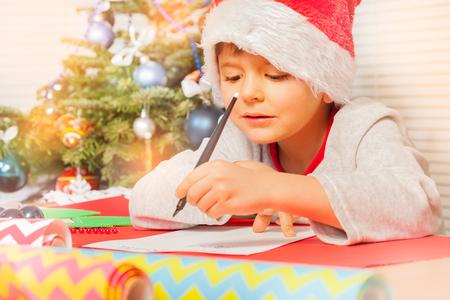 Cute little boy writing letter to Santa Claus