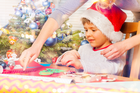 Woman helping her son to decorate holiday ornament Stock Photo