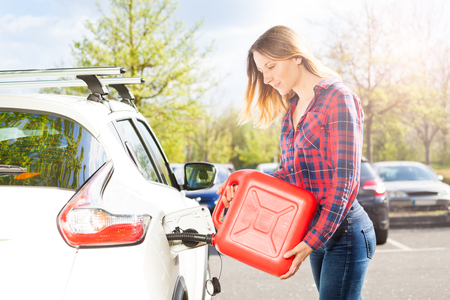 Attractive woman with plastic can filling car tank