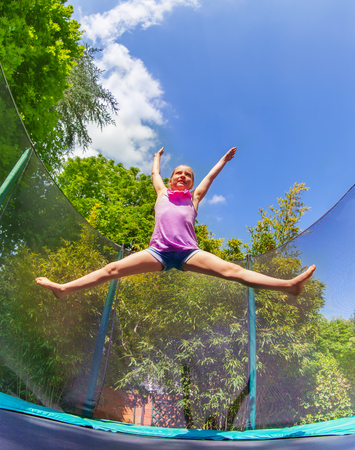 Girl acrobat split jumping on outdoor trampoline Stock Photo