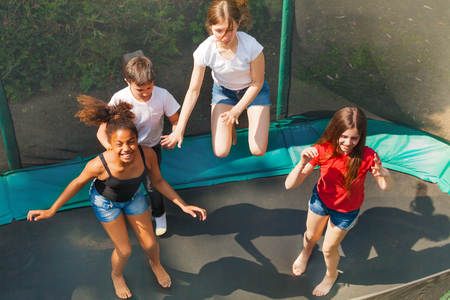 Four happy friends bouncing on outdoor trampoline