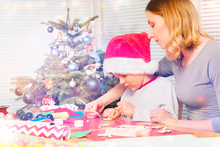 Teacher helping boy to decorate Christmas ornament Stock Photo