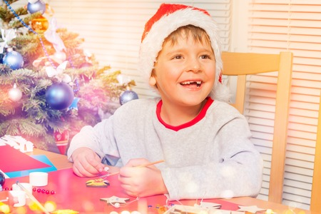Cute boy making own Christmas ornaments at home